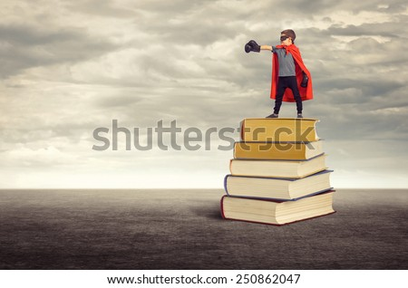 Education. Super hero boy standing on a pile of books in the open air. - stock photo