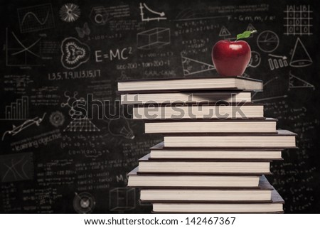Education symbol of apple and stack of books in class - stock photo