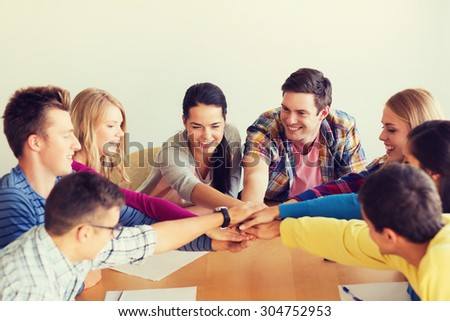 education, teamwork and people concept - smiling students with papers putting hands on top of each other - stock photo