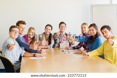education, teamwork, gesture and people concept - smiling students with papers showing thumbs up and sitting at table - stock photo