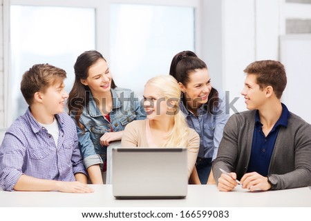 education, technology and internet concept - smiling students with laptop at school looking at each other - stock photo