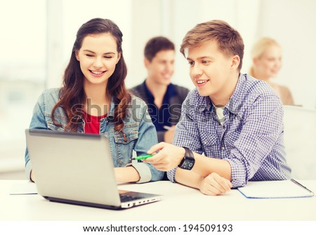 education, technology and internet concept - two smiling students with laptop and notebooks at school - stock photo