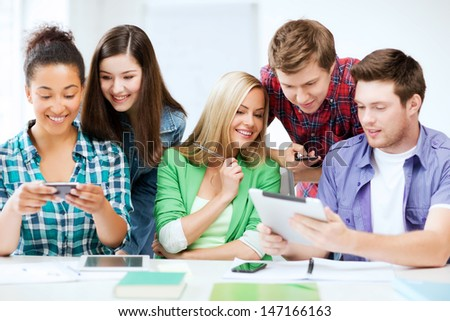 education, technology and internet - students looking at smartphones and tablet pc - stock photo