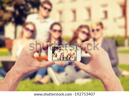 education, technology, summer holidays and teenage concept - close up of hands making picture of group of teens - stock photo