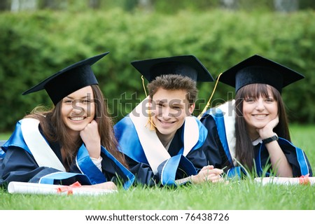 education theme of graduate students lying in the park cheerful and happy - stock photo