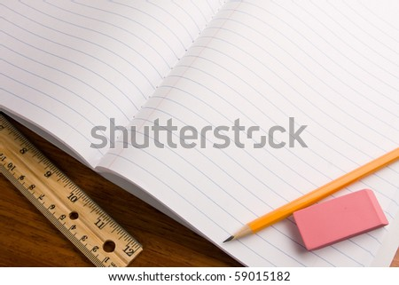 Education topic. Close up of notebook with pencil and eraser on top and a ruler on the side. - stock photo