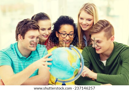 education, travel and geography concept - five smiling student looking at earth globe at school - stock photo