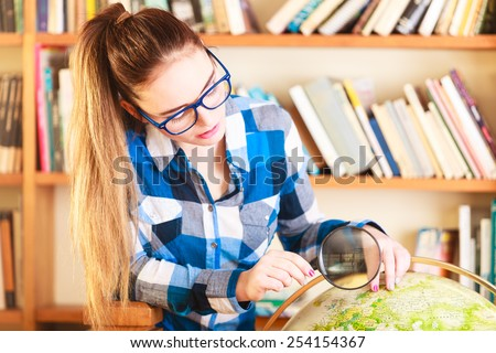 Education travel and geography concept. Young lovely woman female student in blue glasses in library pointing to globe - stock photo