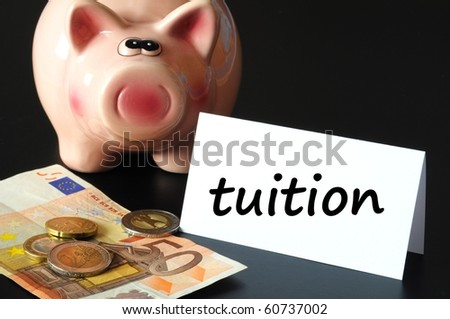 education tuition concept with piggy bank on black background - stock photo