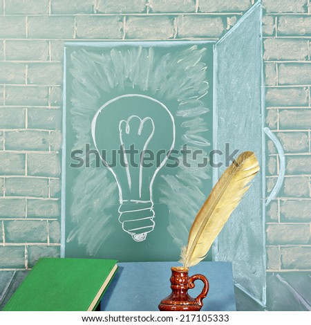 Education unusual concept. Blackboard with drawing of bulb and books with quill pen - stock photo