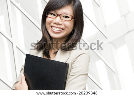 Educational / business people. Young Asian women holding a file in office environment. - stock photo