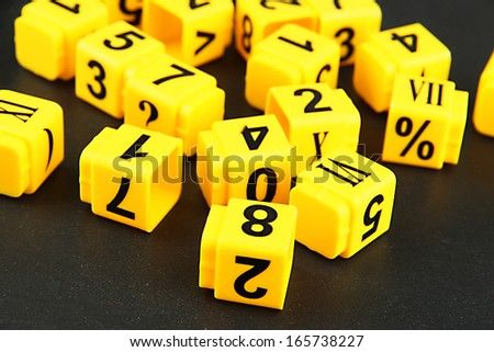 Educational cubes with different numbers on black board - stock photo