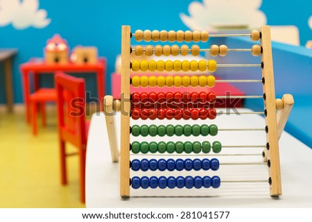 Educational toy for babies inside colorful room with red chairs and blue wall - Multicolor wooden abacus on the white desk - Concept of education learning and teaching - Main focus on red balls - stock photo