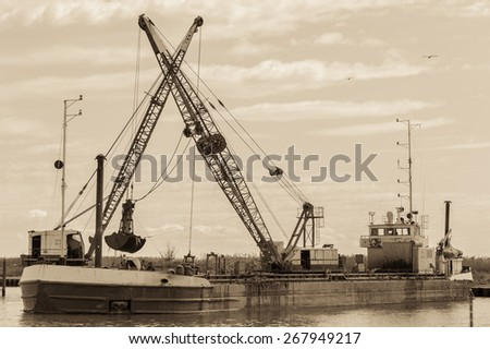 Effect vintage. Small dredge the marina, which is cleaning a navigation channel - stock photo
