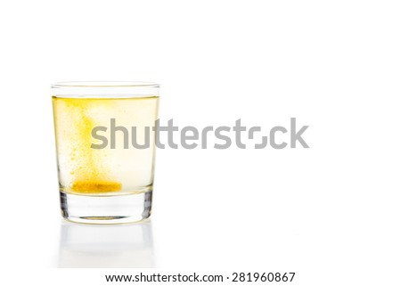 Effervescent vitamin C tablet bubbles in glass of water - stock photo