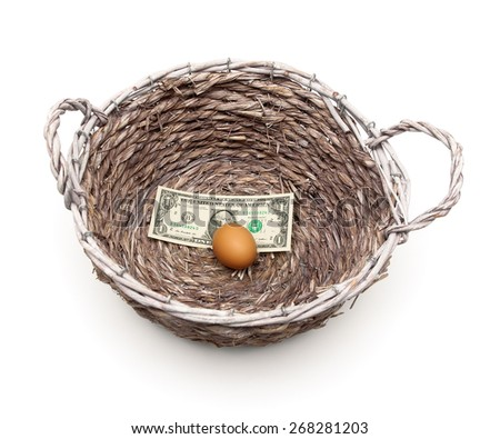 egg and dollar in a basket on a white background. horizontal photo. - stock photo