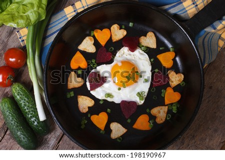 Egg and vegetables in the shape of heart. top view of the pan. Valentine's Day  - stock photo