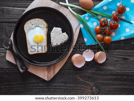 Egg baked in a bread in a heart shape on a cast iron skillet. Fried eggs, cherry tomatoes, green onions. A hearty breakfast in a rustic style. Top view. - stock photo