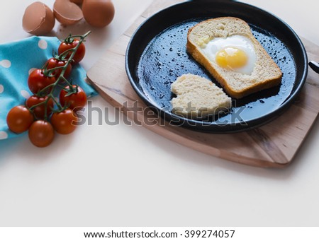 Egg baked in a bread in a heart shape on a cast iron skillet. Fried eggs, cherry tomatoes, green onions. Breakfast in a rustic style. - stock photo