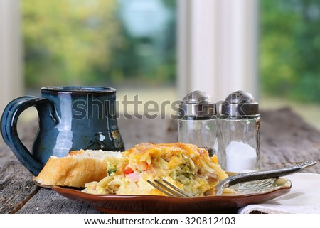 Egg, cheese, peppers, onion and sausage breakfast casserole served with coffee on  a rustic table plate, fork and napkin - stock photo