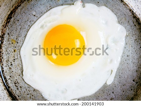 Egg fried on an old frying pan. - stock photo