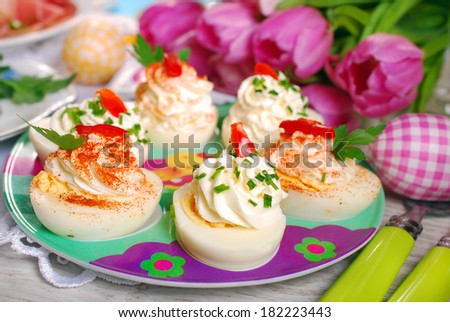 egg halves stuffed with cheese and mayonnaise decorated with red pepper and chives for easter - stock photo