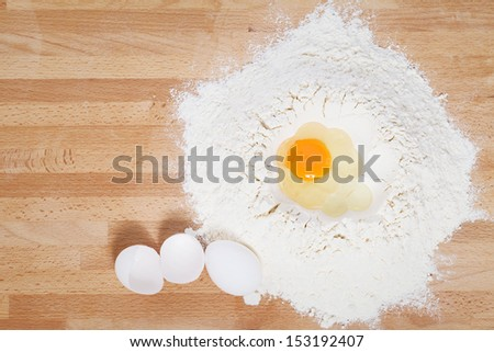 egg in flour from top with egg and broken egg aside on wooden background - stock photo