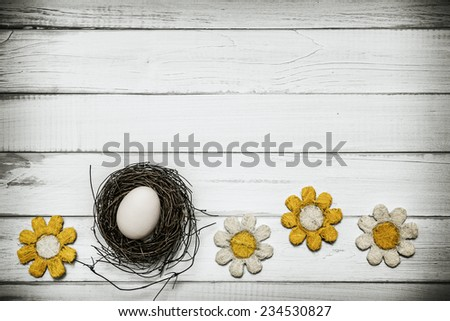 Egg in nest with flowers around on wooden background -Concept that announces spring and Easter holidays - stock photo