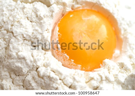egg into the flour - stock photo