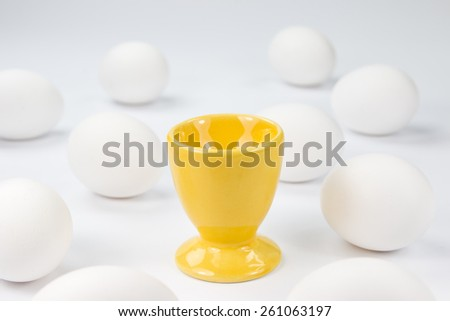 Egg on a yellow stand among white eggs on a white background - stock photo