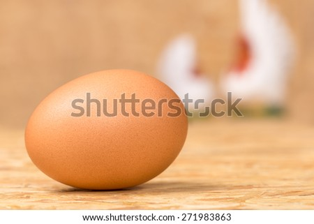 Egg on plywood  floor with white hen and chicken blur on  background - stock photo