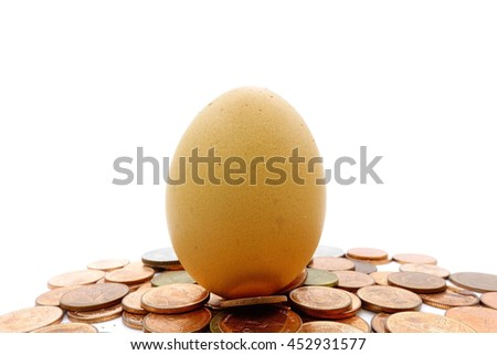 egg over thai coins on white background,select focus with shallow depth of field - stock photo