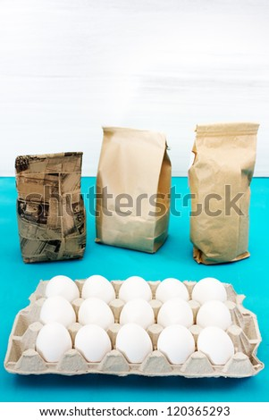 Egg set with three paper packs, on white and blue background - stock photo
