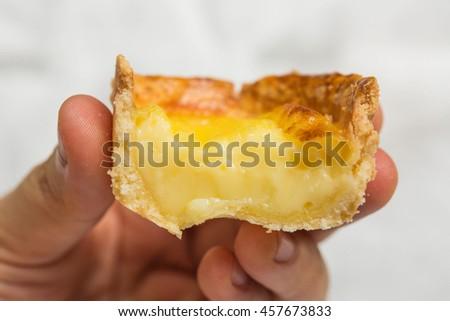Egg Tart. Egg Custard Tart. Asian Famous Dessert, Crispy and Melt. Homemade Fresh Baked. Hand Holding, Eating. Selective, Close up. - stock photo