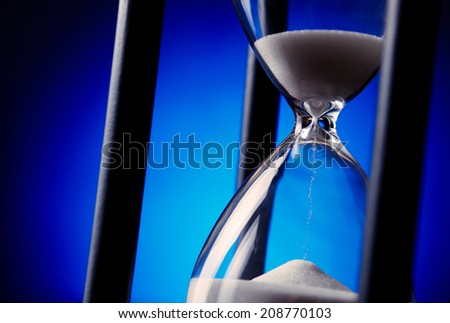 Egg timer or hourglass with blue sand running through the glass bulbs in a concept of passing time and time management - stock photo