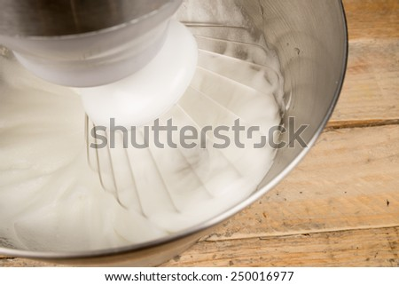 Egg whites being whisked inside a modern food processor - stock photo