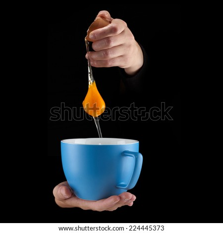Egg Yolk dripping, falling in to cup, on black background. - stock photo
