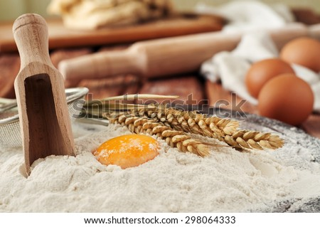 Egg yolk in flour close up on a wooden table in a bakery. Rural or rustic style. Copy space. Free space for text - stock photo