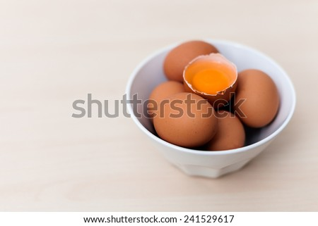 Egg yolk on a egg pile on a wooden backgroung - stock photo