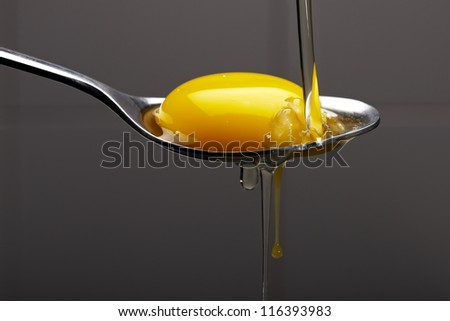 Egg yolk on a silver spoon, seperating protein - stock photo