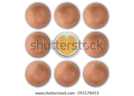 Eggcups full of fresh free range Chicken eggs with one cross section showing boiled heart shaped egg yolk and egg white, isolated on white background - stock photo