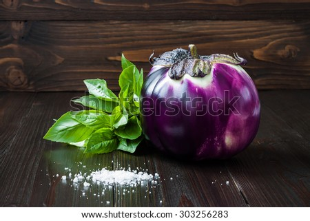 Eggplant (aubergine) and basil on dark wooden table. Fresh raw farm vegetables - harvest from the garden in rustic kitchen. Rural still life - stock photo