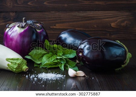 Eggplant (aubergine) with basil and garlic on dark wooden table. Fresh raw farm vegetables - harvest from the garden in rustic kitchen. Rural still life - stock photo