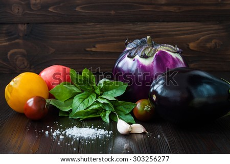 Eggplant (aubergine) with basil, garlic and tomatoes on dark wooden table. Fresh raw farm vegetables - harvest from the garden in rustic kitchen. Rural still life - stock photo