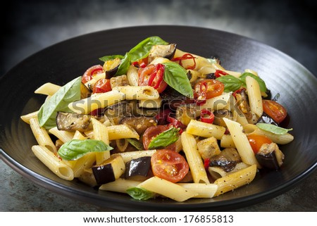 Eggplant, chilli and tomato penne pasta, on a black serving platter.  Garnished with basil. - stock photo