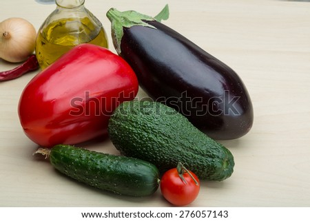 Eggplant, cucumber, avocado and red pepper on the wood background - stock photo