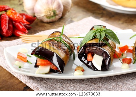 Eggplant rolls with cheese, tomato and basil on complex background - stock photo