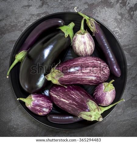 Eggplant varieties in black bowl over dark slate background.  Overhead view. - stock photo