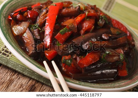 Eggplants fried with vegetables in a Korean-style close-up on a plate. horizontal