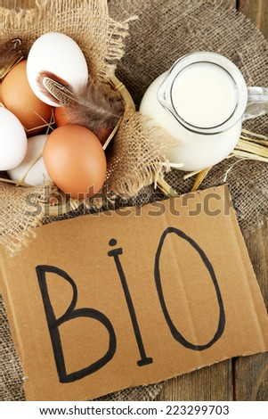 Eggs and fresh milk in glass jug with inscription BIO  , on wooden background. Organic products concept - stock photo